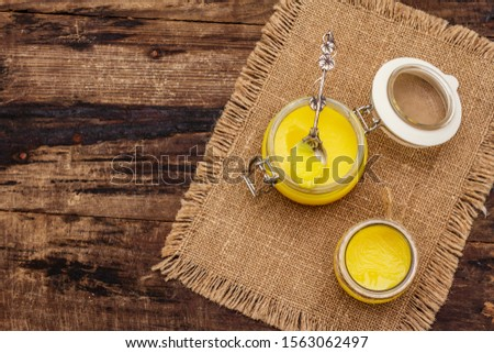 Pure or desi ghee (ghi), clarified melted butter. Healthy fats bulletproof diet concept or paleo style plan. Glass jars, silver spoon on vintage sackcloth. Wooden boards background copy space top view #1563062497