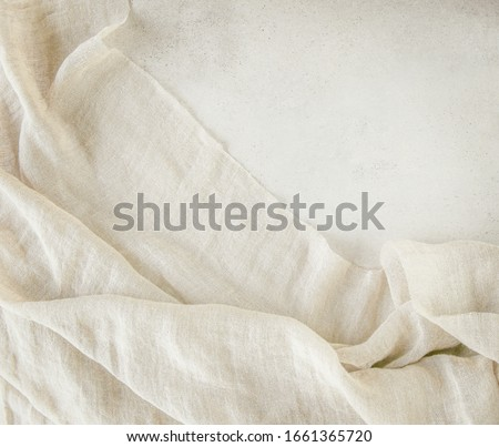 Pure washed linen cloth on light grunge stone background. Natural washed linen fabric on stone tile surface with copy space. Stock photo ©