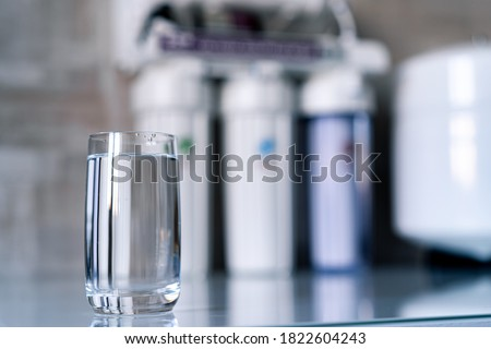 Pure water in glass and water filters on the blurred background. Household filtration system.