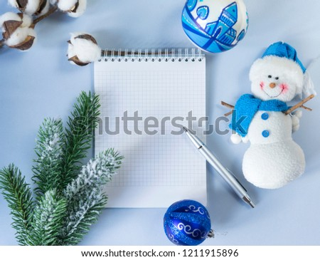 pure white Notepad sheet, place for lettering, silver handle, green spruce branch, cotton branch, 2 blue  balls, snowman on blue background, top view, close up, snowman, blue Christmas ball, flat lay
