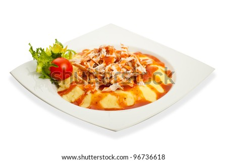 Puree with chicken piece and sause on a plateau isolated on white background