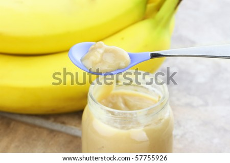 Pureed baby food from a jar with fresh bananas in background.