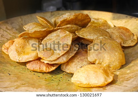 Puri (poori) , tasty Indian  bread,  on the copper pan