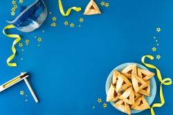 Purim celebration concept (jewish carnival holiday) on blue background, top view, copy space. Flat lay with hamantaschen cookies and  mask.