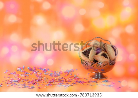 Purim holiday concept with confetti, hamantaschen cookies or hamans ears or ozney haman in hebrew over bokeh lights background. #780713935
