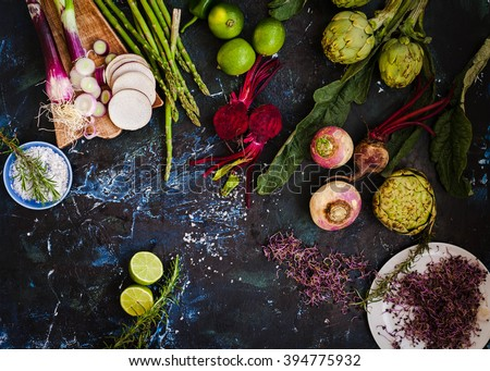 Purple and green veggies and roots composition on a dark slate table. Artichoke, Beetroot, red onion, radish, asparagus ready to prepare salad. detox and diet food. Stock photo ©