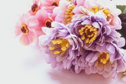 Purple and pink artificial flowers on grey background