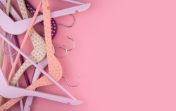 Purple and pink wooden clothes hangers on a pink background copy space.