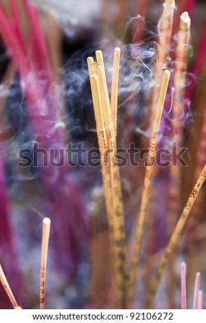 Purple and yellow incense sticks burning at an altar of a Taoist temple, Beijing, China