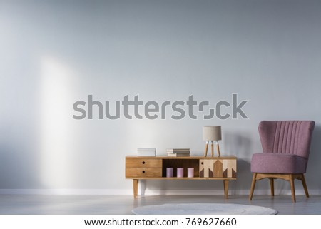 Purple armchair next to wooden cupboard with books, candles and lamp against wall with copy space in kid's room interior
