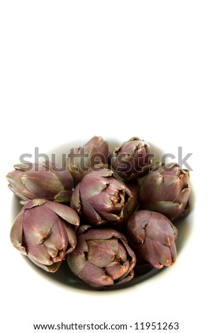 purple artichokes in a bowl, isolated on white background