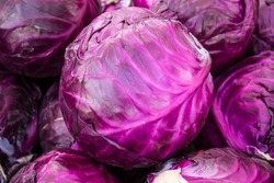 Purple cabbages stacked at a farmers' market