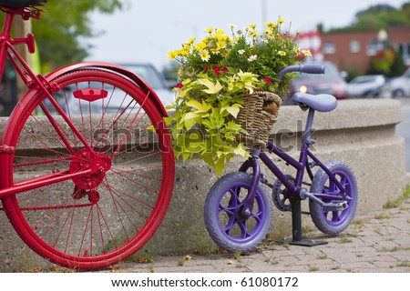 Purple child's bike behind an adult's bike as decoration