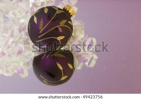 purple Christmas bauble with gold leaves and pearl white metallic ribbon on a soft purple background