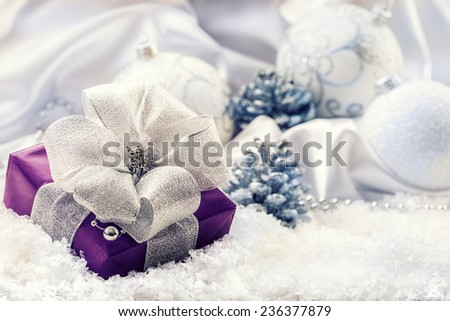 Purple Christmas gift,package with a silver ribbon and background christmas decoration - Christmas balls pine cone white satin and white snow - snowflakes.Christmas time.