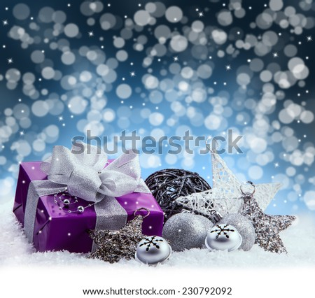 Purple Christmas package , gift of a silver ribbon. Jingle bells , silver christmas balls and christmas stars put on snow. Abstract multicolored blurred background space.