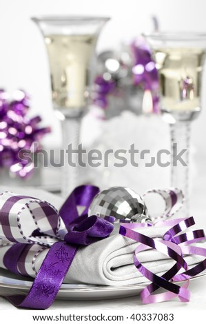 Purple Christmas table setting with napkin and glasses of white wine