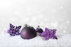 Purple christmas tree decoration, baubles and stars, on snow, background, copy or text space