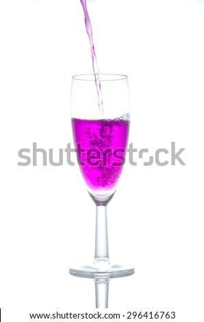 purple cocktail in glass isolated on white background, purple water flows into the glass and makes bubbles isolate on white background