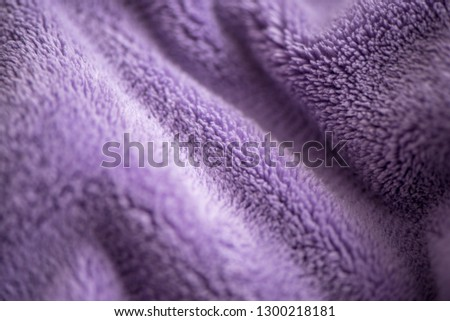 Purple delicate  background of nice furry cloth. Soft loose folds on the fabric of faux fur of lilac color as a textured background. Details of warm winter clothes, lining fabric, closeup