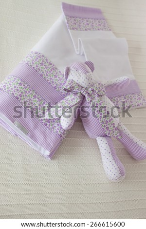 Purple dish cloth and rabbit toy on white linen towel