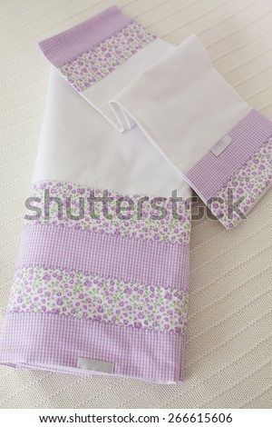 Purple dish cloth folded on white linen towel