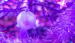 Purple festive Christmas background with xmas ball and tinsel on Christmas Tree. Copy space, selective focus.