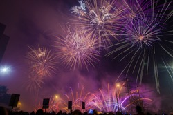 Purple festive fireworks on a black background. Abstract holiday background. International Fireworks Festival in Moscow