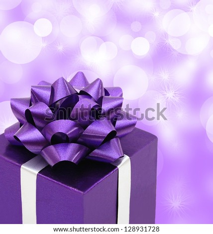 Purple gift box with gift ribbon isolated on purple background - stock photo