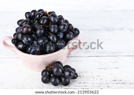 Purple grapes in bowl on wooden background