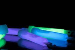 Purple, green and blue glowsticks on a reflective surface