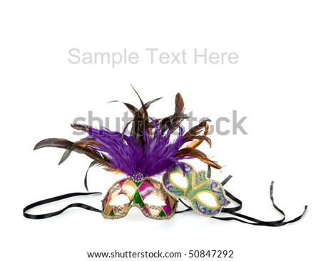 Purple, green and gold mardi gras masks on a white background with copy space