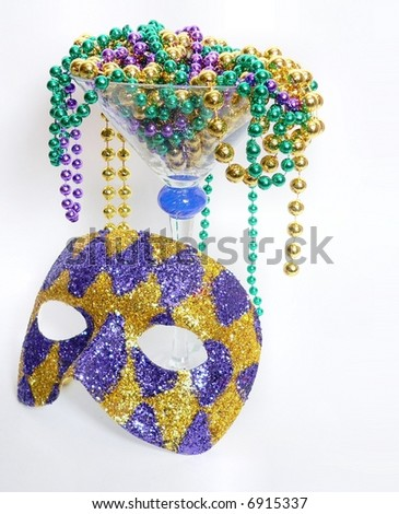 Purple, green and gold mardis gras beads overflow a large martini glass with a purple and gold harlquin mask leaning again the stem of the glass.  Vertical image on white with copy space