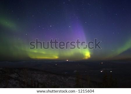 Purple-green-yellowish northern lights in starry sky over hill terrain litted with moonlight. April 2006, near Fairbanks, AK. (some noise) - stock photo