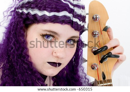 Purple hair and purple eyes.  Goth teen girl bass player shot in studio over white.