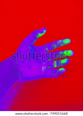 Purple hand stained green on Red background , Hand in Gamma radiation /gamma ray effect  , neon effect  #749051668