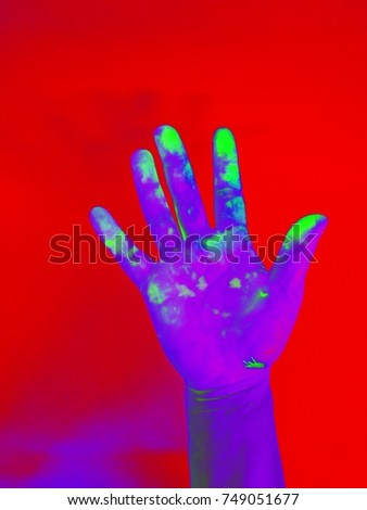 Purple hand stained green on Red background , Hand in Gamma radiation /gamma ray effect  , neon effect  #749051677