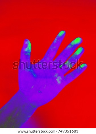 Purple hand stained green on Red background , Hand in Gamma radiation /gamma ray effect  , neon effect  #749051683