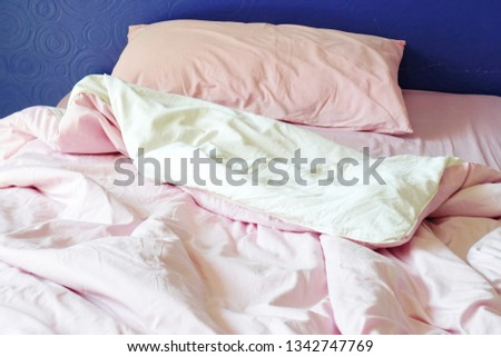 purple headboard, messy soft pink bedding sheets and pillows in the morning #1342747769