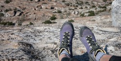 Purple hiker's boot hanging over rocky ledge with giant stone filled valley below