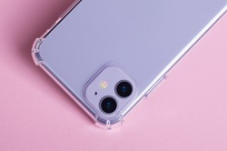 Purple iPhone 11 in clear case isolated on pink background close up back view. Phone case mock up