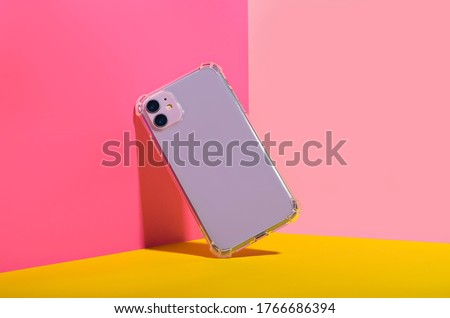Photo of  Purple iPhone 11 in clear phone case, bright and colorful phone case mock up