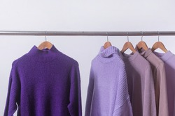 Purple Knitted, sweaters hang on hangers. Bright sweaters. Fashion.