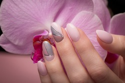 Purple neat manicure on female hands on a background of flowers. Nail design
