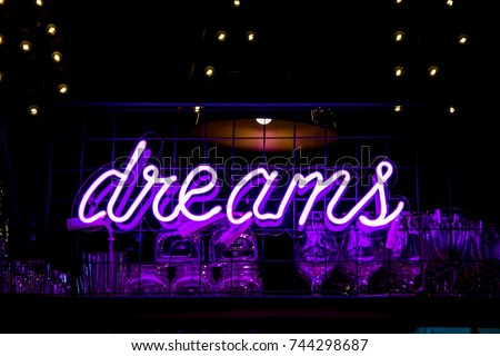 Purple Neon Inscription DREAMS and glasses on blurred lights background. Dark tones vintage image. #744298687