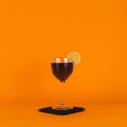 Purple Nick and Nora cocktail in a orange studio background