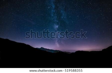 purple night sky stars. Milky way galaxy across mountains.