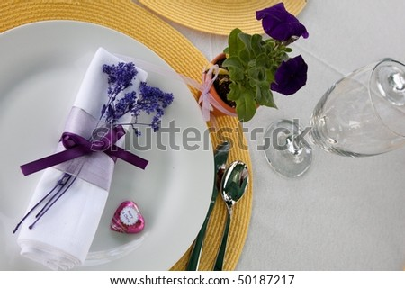 stock photo Purple or violet wedding place setting with yellow place mats