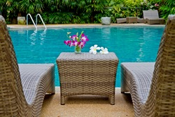 Purple orchid and Frangipani flowers with Rattan chair side swimming pool