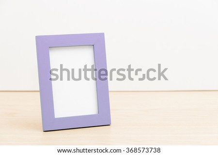 purple photo frame on wooden table white background